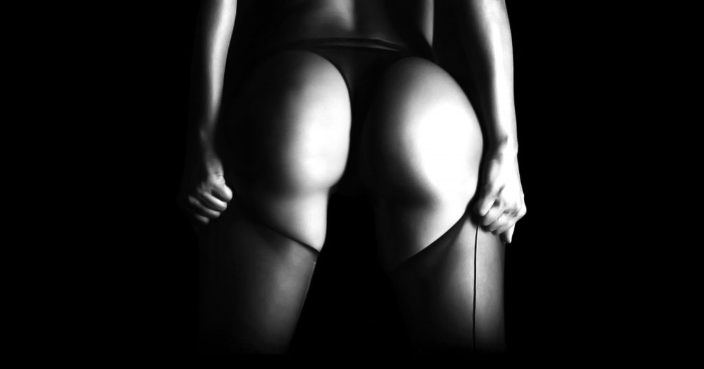 Beginners Guide to Spanking Black and white image of bare buttocks and fishnet stockings.